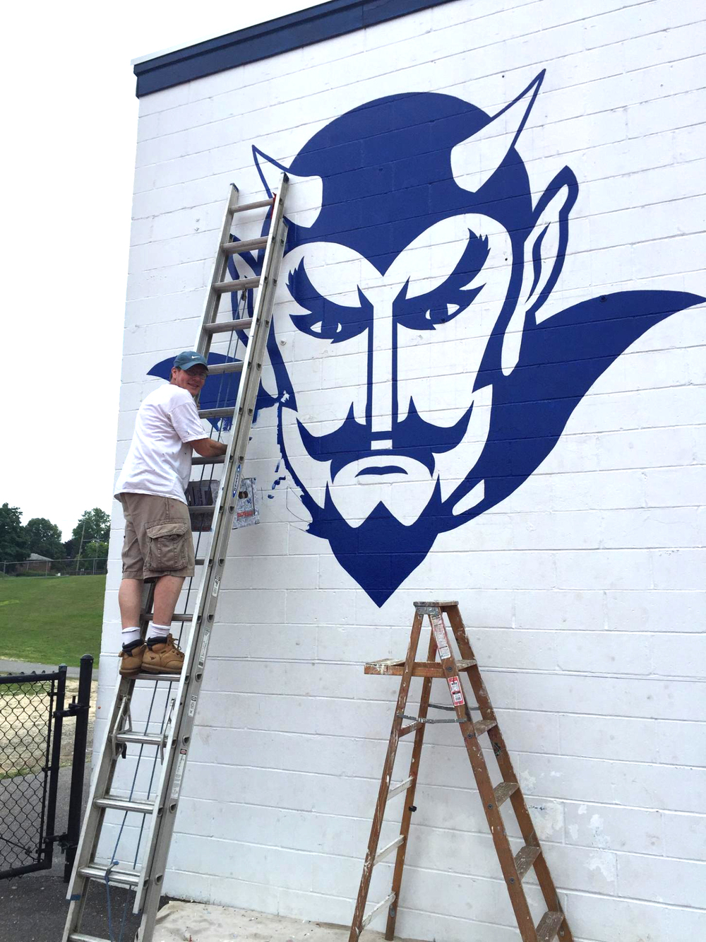 David Whitcher paints Huntington High School's logo onto the field house.