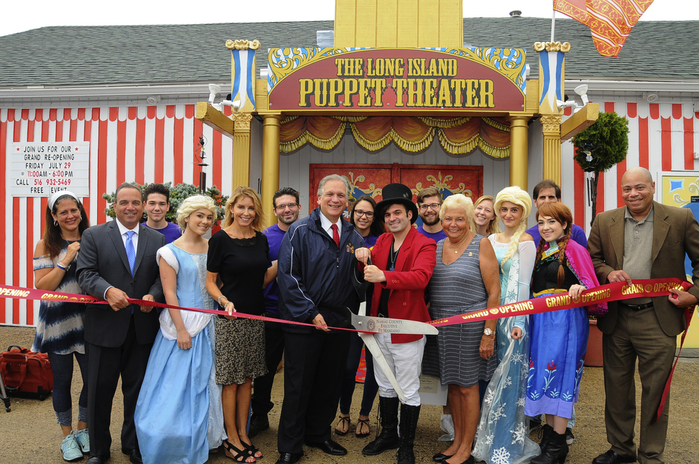 New owner of The Long Island Puppet Theater Anthony Labriola and Nassau Executive Edward P. Mangano, center, are pictured cutting the ceremonial ribbon last Friday. They're pictured with Nassau legislators Laura Schaefer and Rose Marie Walker; Lionel Chitty, president of the Hicksville Chamber of Commerce; former Town of Oyster Bay Clerk Steve Labriola; Tori Kalberer, dressed as Elsa; Michaela Vivona, dressed as Anna; Jacklyn Stroud, dressed as Cinderella; Carol and Vin Labriola; and Ryan Garzilli. Photo/Nassau County