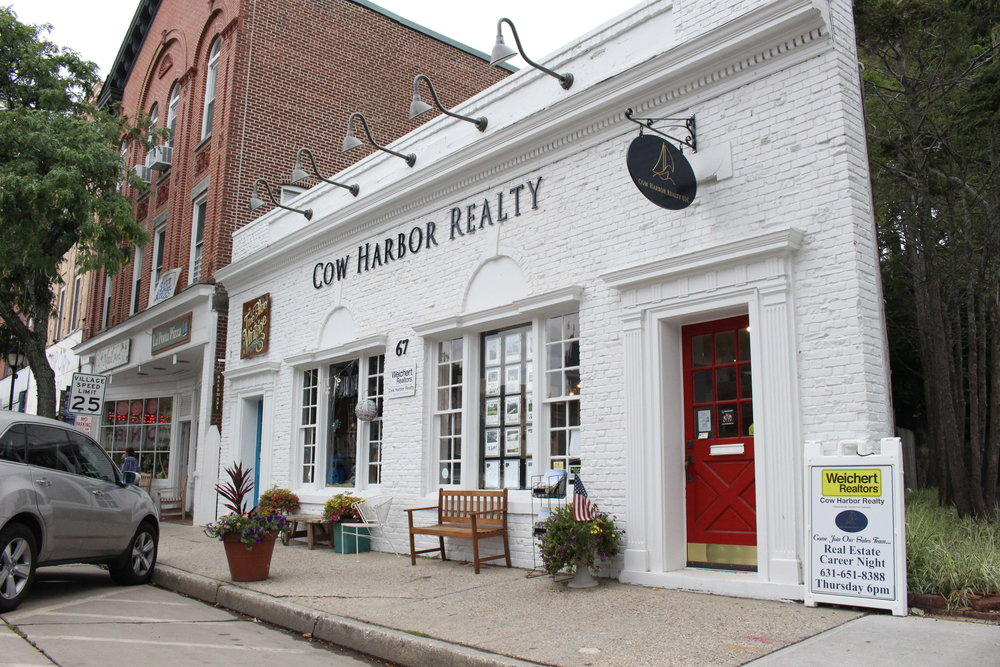 When entering Cow Harbor Realty in Northport, clients are greeted by a red door that pops out along the building that features white bricks with a navy blue accent.