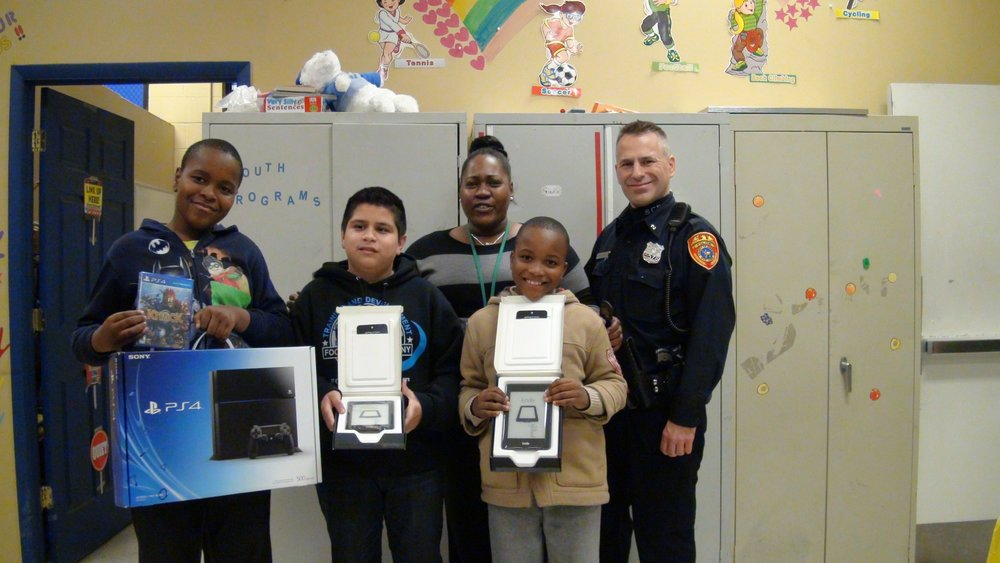 Second Precinct Police Officer Tom Arana-Wolfe, right, is pictured at a December 2013 pizza party where he and the Family Service League gave away a PlayStation 4 video game system and Amazon Kindle e-readers to kids who won the fall reading contest.*Photo courtesy of Tom Arana-Wolfe