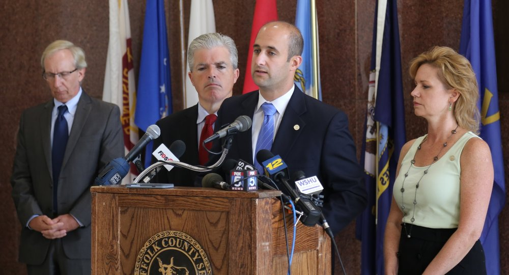 Photo courtesy of Derek Poppe Suffolk Legis. Rob Calarco (D-Patchogue), center, announces with Suffolk Executive Steve Bellone, left-center, the lawsuit filed against various pharmaceutical companies for their alleged role in the county's opiate epidemic.