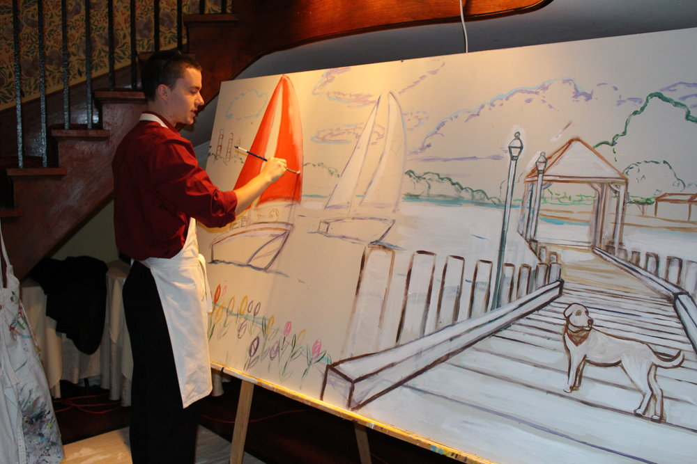 Sean Carlson, a Splashes of Hope volunteer and artist who painted a mural for Thomas Hammerquist, paints a mural during the nonprofit's 20th anniversary gala. Throughout the night, many guests contributed to the painting.