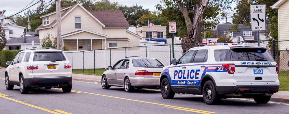 """A Suffolk police officer pulls over a vehicle in Huntington Station on Wednesday. Suffolk Police Commissioner Timothy Sini said police believe there is """"more than one"""" active gang in Huntington Station."""