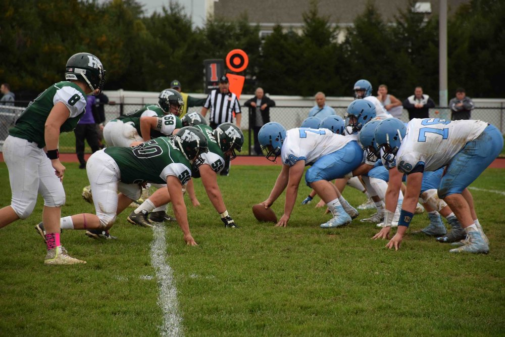 Photos courtesy of the Harborfields School District The Harborfields football team showed persistence and character during their homecoming game, said head coach Rocco Colucci. Above, Harborfields' defensive line, left, tries to stop Rocky Point's offense.