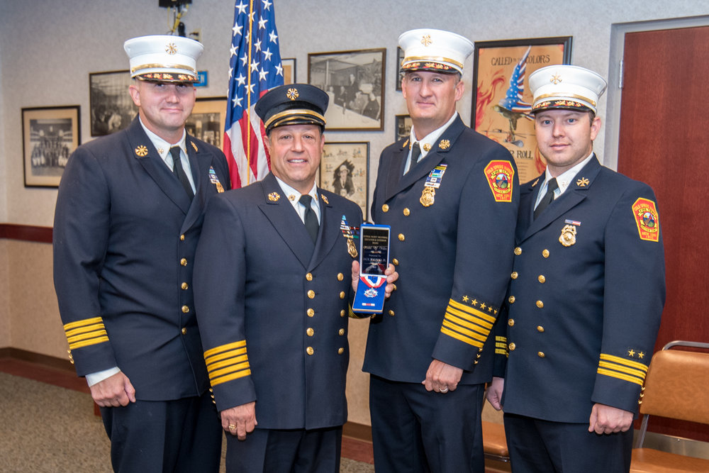 Cold Spring Harbor Fire Department chiefs congratulate Ex-Chief Jack Italiano Jr., who displays his Medal of Valor. Pictured, from left: First Assistant Chief Dan Froehlich, Italiano, Chief Peter Como and Second Assistant Chief Justin Armbruster.