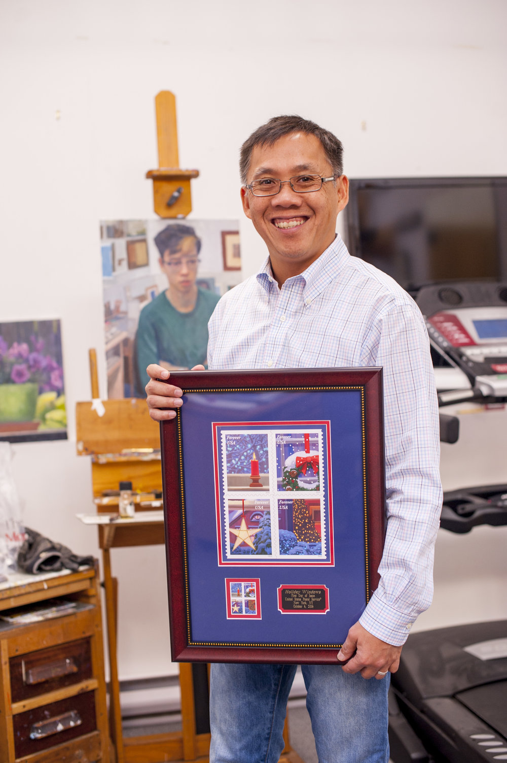 "Huntington illustrator William Low proudly displays his second set of stamps, ""Holiday Windows,"" which were commissioned by the United States Postal Service. Behind him is a painting of his son, Timothy."
