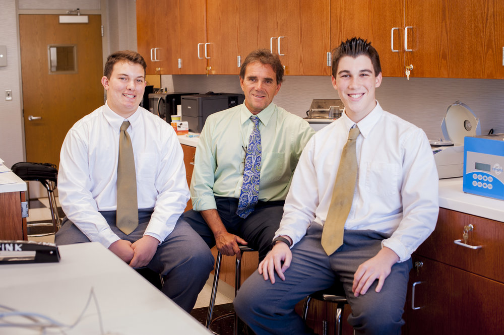 Siemens competition semi-finalists Nicholas DeFrancisco, left, and Christopher Koch, right, sit with St. Antony's High School Science Research Director Paul Paino in the school's new molecular biology lab.