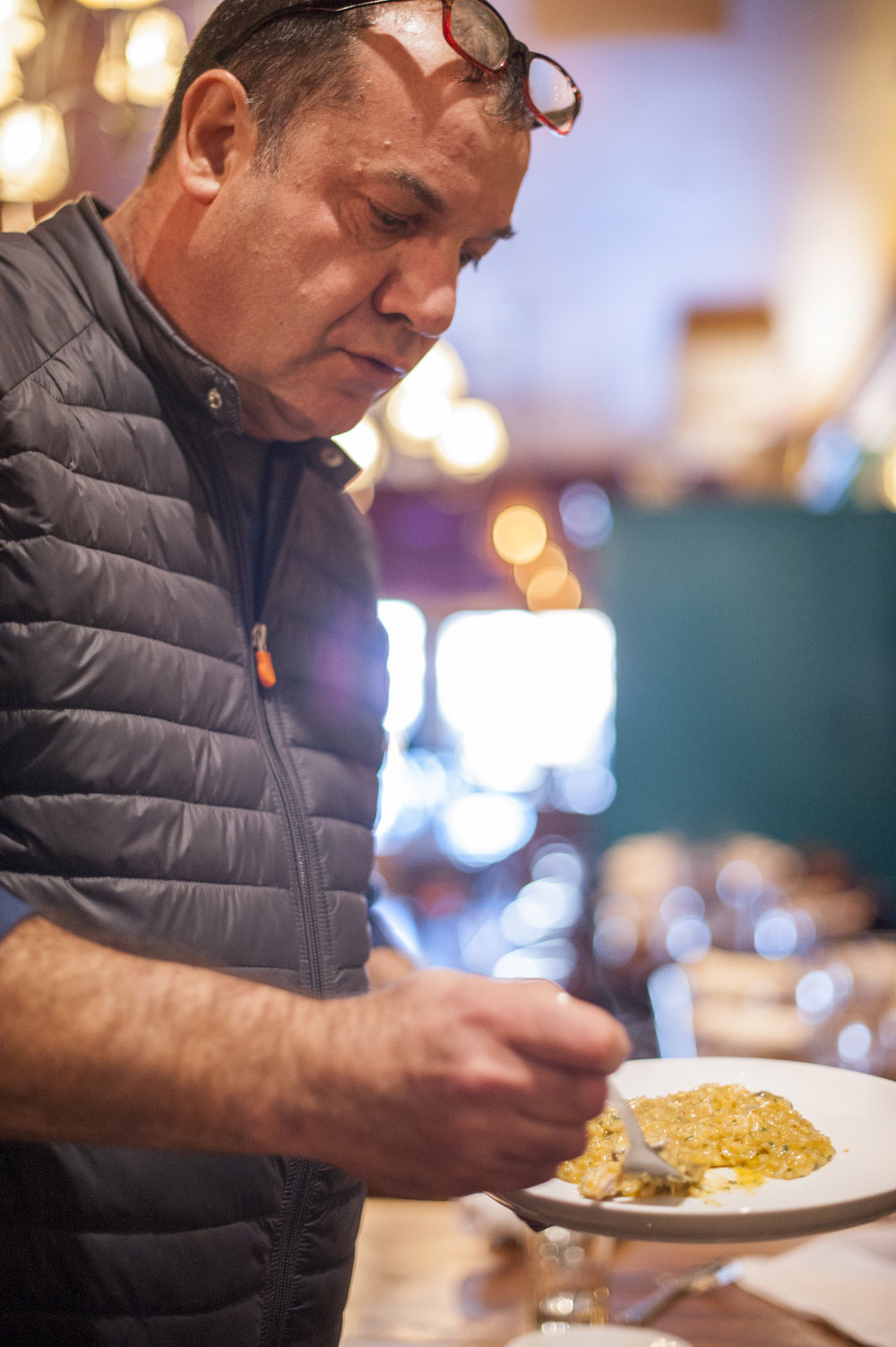 Nino Antuzzi, owner of Osteria Da Nino, samples a seafood risotto to ensure the finest quality in his cuisine.