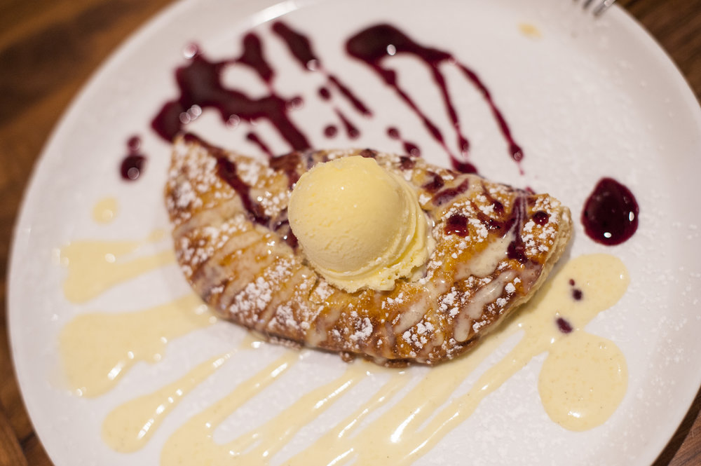 The warm and flakey Apple Turnover is topped with vanilla gelato, paired with raspberry and custard sauce.