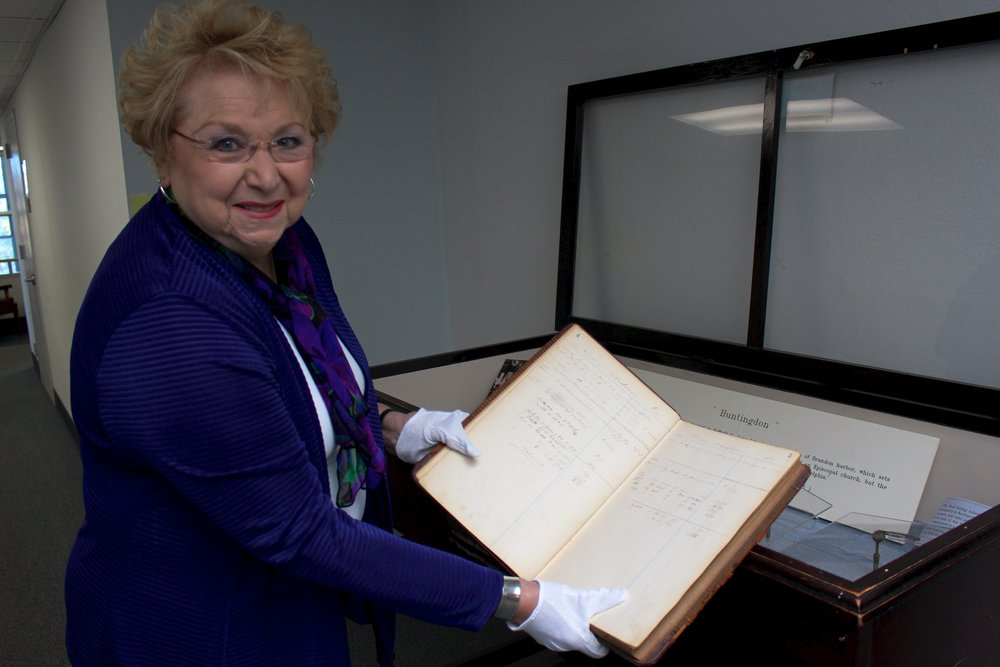 "Jo-Ann Raia, Huntington town clerk, holding up a book on oyster lot rents in Northport from 1887-1897, which can be viewed on display in town hall's ""A Sea of History-Our Maritime Heritage"" exhibit."