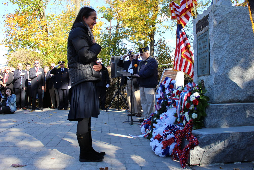 Laura Kasa holds her hand over her heart after placing a red star wreath in honor of her father, Roger Kasa, a U.S. Army Vietnam War veteran who passed away over the summer.