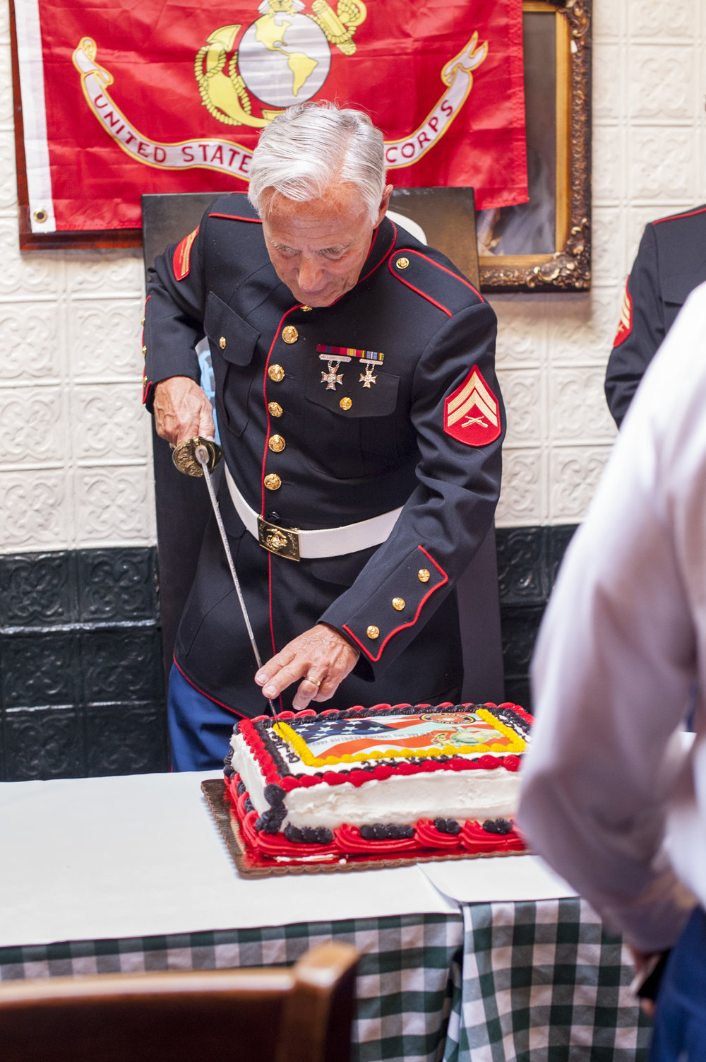William Ober, past commandant of the Marine Corps League of Huntington, cuts the cake halfway to pass on to the sword to the youngest member.