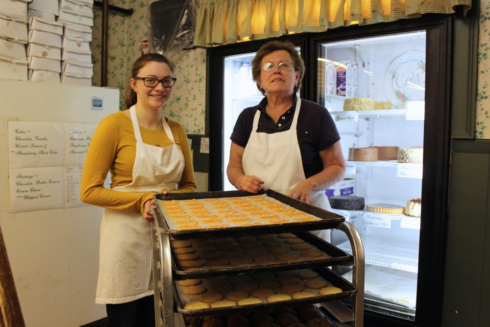 Mary McDonald, right, owner of A Rise Above Bake Shop, stands with employee Hana Fulfarr in front of cookies that the bake shop prepared for the day ahead.