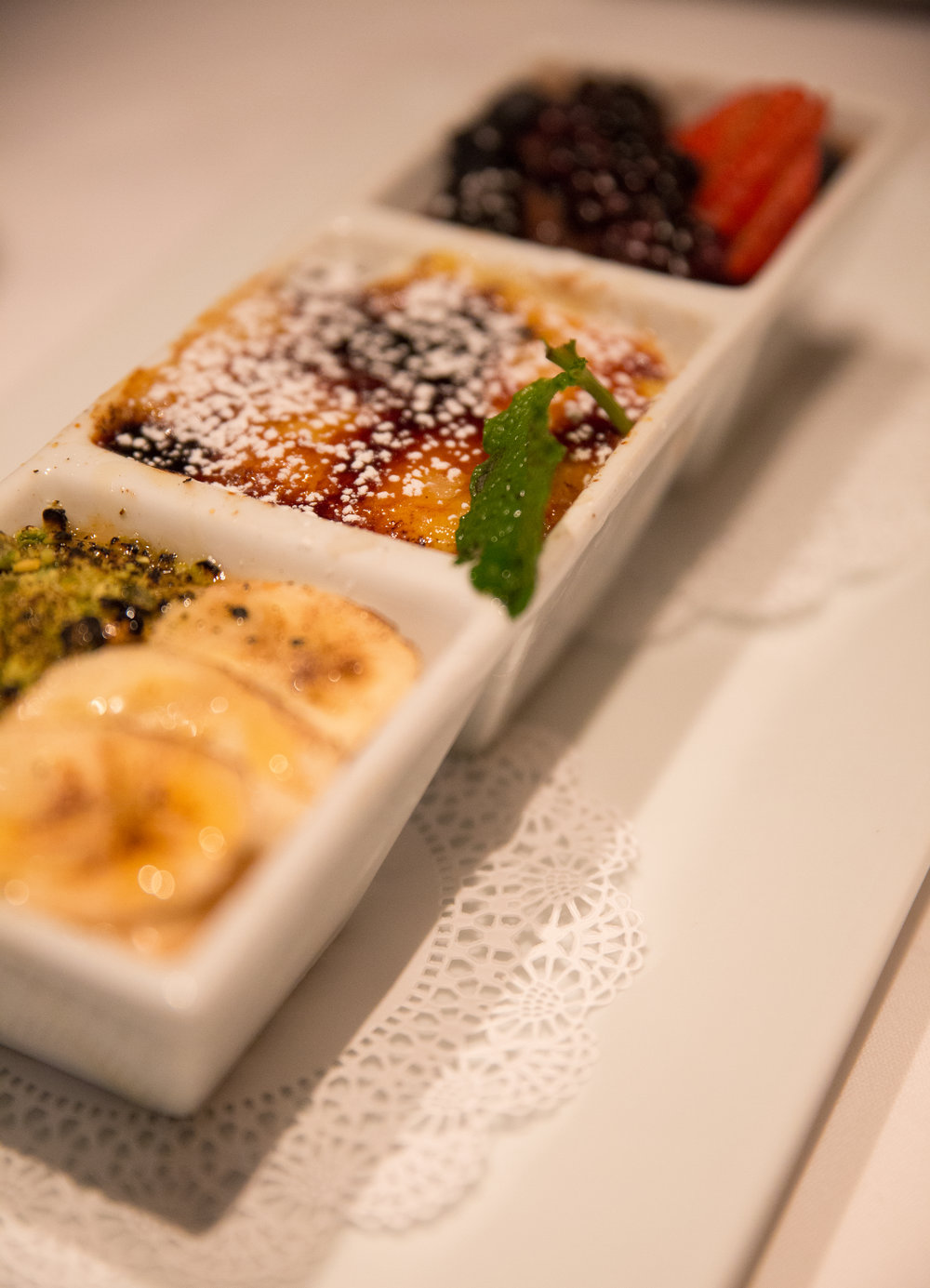 The triple Creme Brulee brings together the classic creme brulee, another one that is mango flavored and topped with banana and ground pistachio and a third that's blended with chocolate and is topped with blueberries, blackberries and strawberries. (Photo / Craig D'Andrea).
