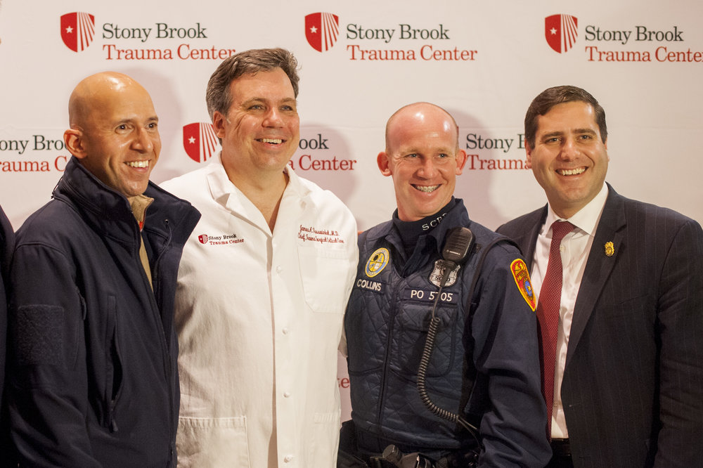 Stony Brook University Hospital Chief Trauma Surgeon Dr. James Vosswinkel, second from left, will be honored at the New York Jets game for saving the lives of Suffolk police officers Det. Nicholas Guerrero, left, and officer Mark Collins, second from right, who will also be honored. They stand next to SCPD Commissioner Timothy Sini.