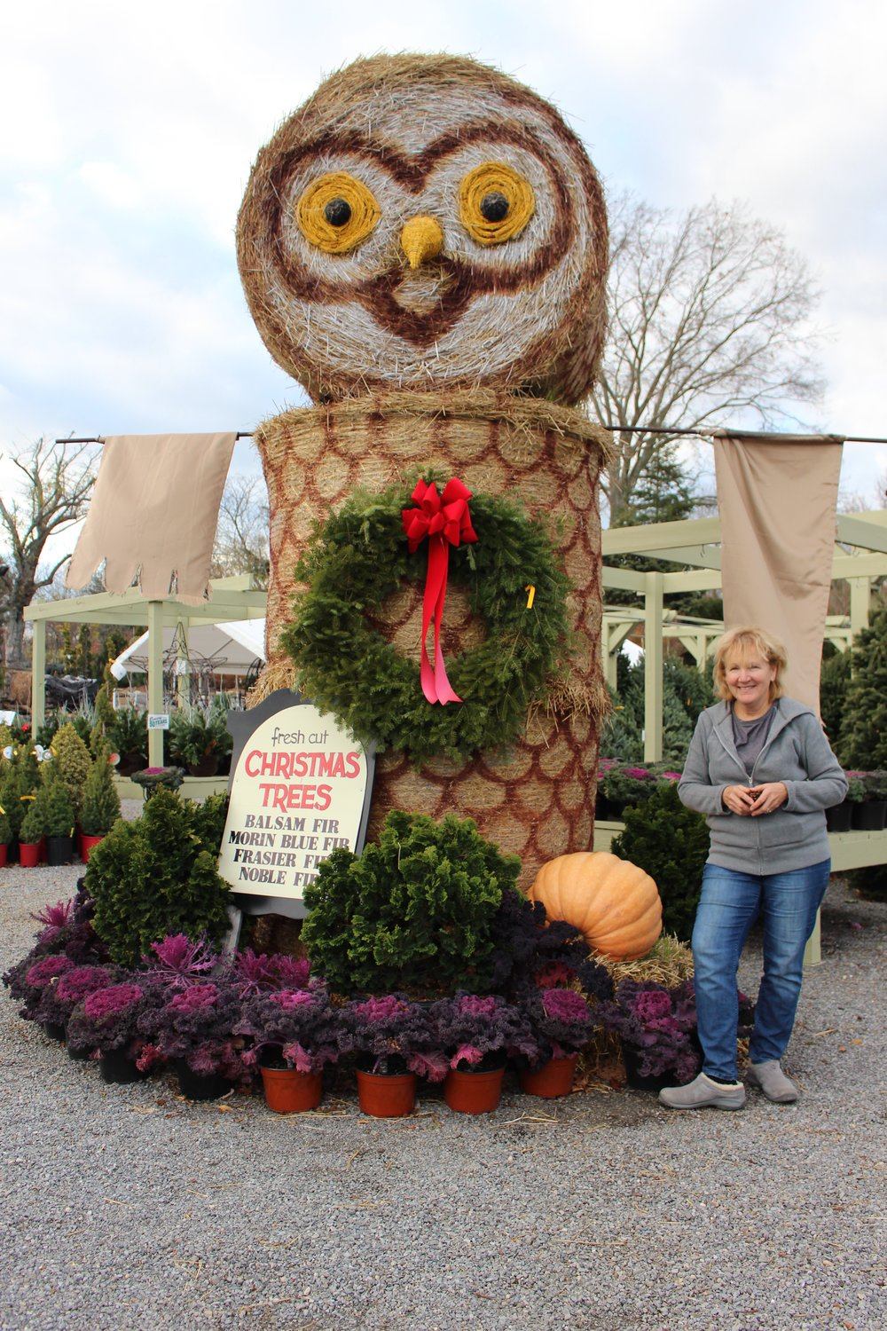 Donna Bemiss, owner of Oakwood Road Nursery, stands next to a giant owl made from hay and a sign listing the types of trees the nursery offers this holiday season.
