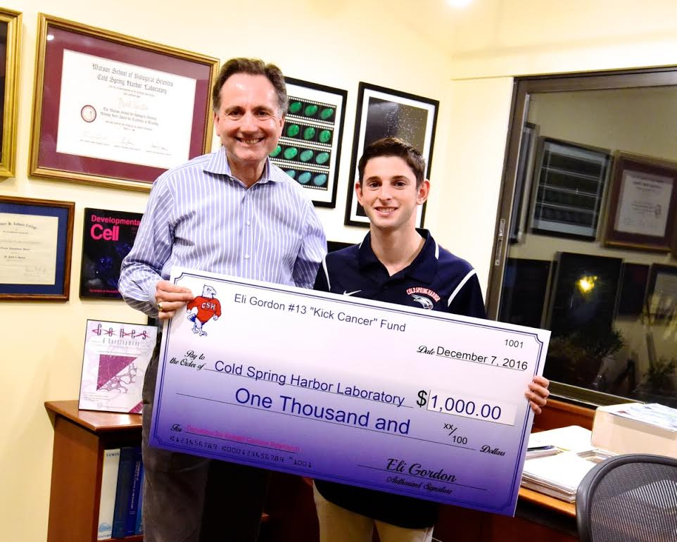 "Eli Gordon, right, a junior at Cold Spring Harbor Jr./Sr. High School, presented a $1,000 check to Dr. David Spector, left, Director of Research and Professor at Cold Spring Harbor Labs, after raising the funds throughout his ""Kick Cancer"" initiative.  (Photo by Howard Gordon)."