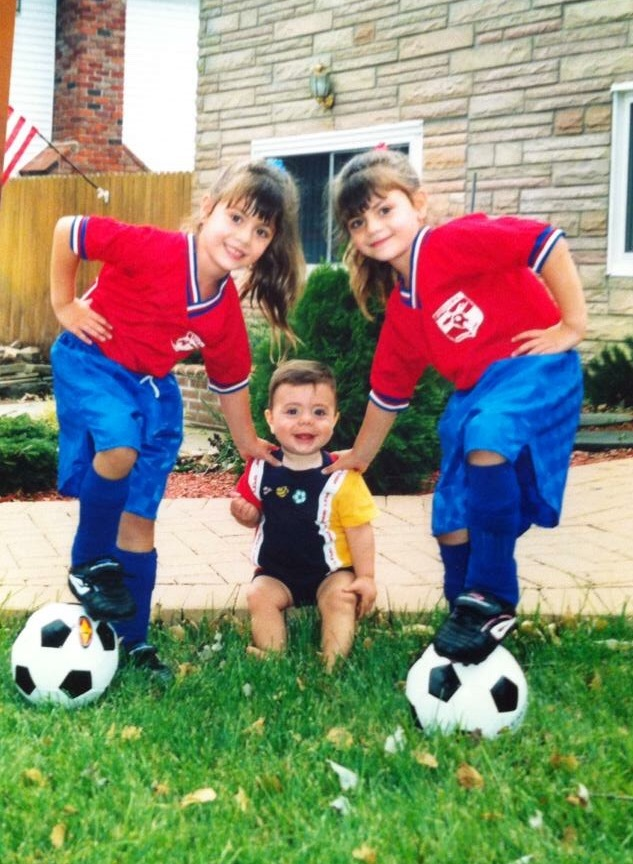 Pictured at 5 years old, Arianna, left, and Olivia, right, pose in their Levittown soccer jerseys with younger brother Dante.