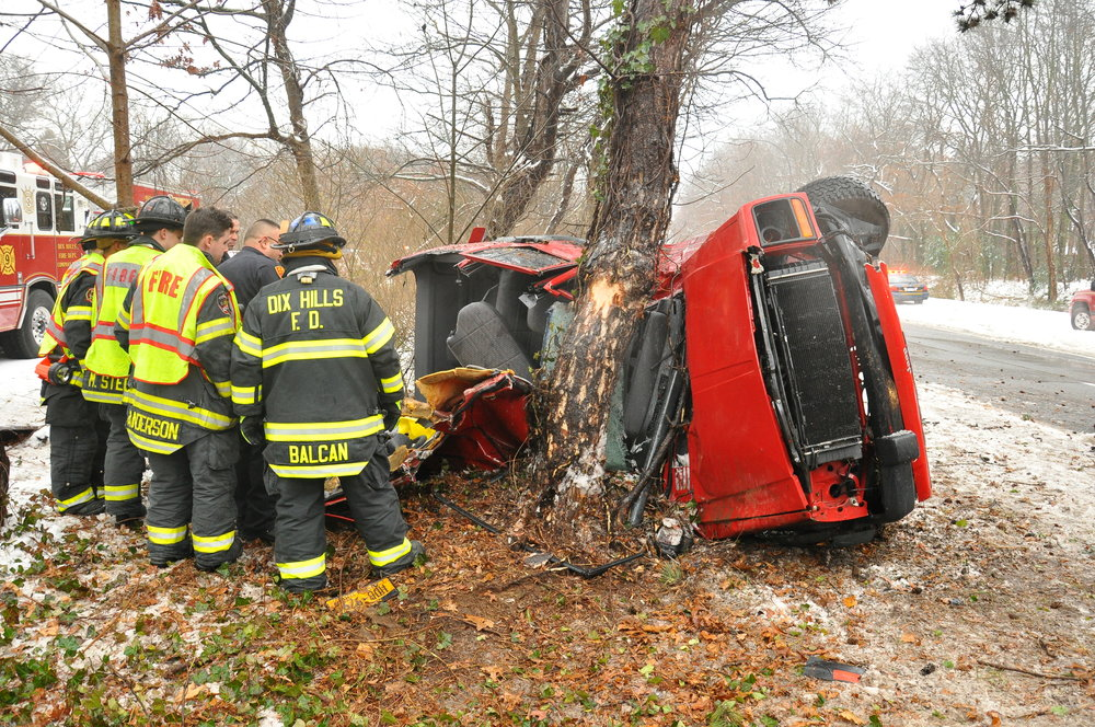 First responders examine a Jeep that overturned and crashed into a tree along the Northern State Parkway in Dix Hills on Saturday. Twenty-two-year-old Thomas Hardy, of East Northport, the driver, was killed in the crash, which also injured a male passenger. (Photo by Steve Silverman).