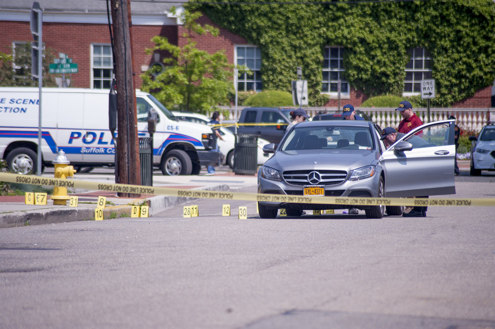 Suffolk police officials search the Mercedes of Edwin Rivera, who was found on Clinton Avenue in Huntington village in a pool of his own blood, early in the morning of May 25.