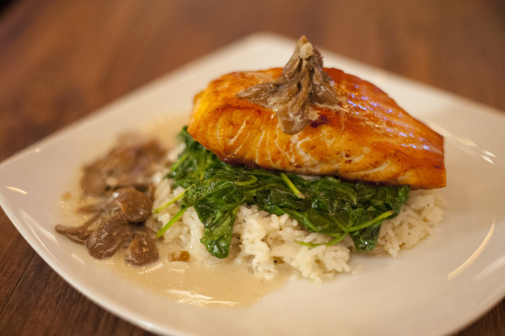 The Roasted Salmon Filet at Crabtrees, served on a bed of spinach and jasmine rice, is served with maitake mushrooms and an Irish cream sauce that makes this a true comfort meal.
