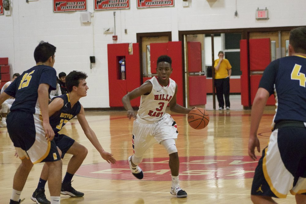 Hills East's Savion Lewis (no. 3) dribbles the basketball up the court during the second quarter of Tuesday night's game between the Thunderbirds and Northport.