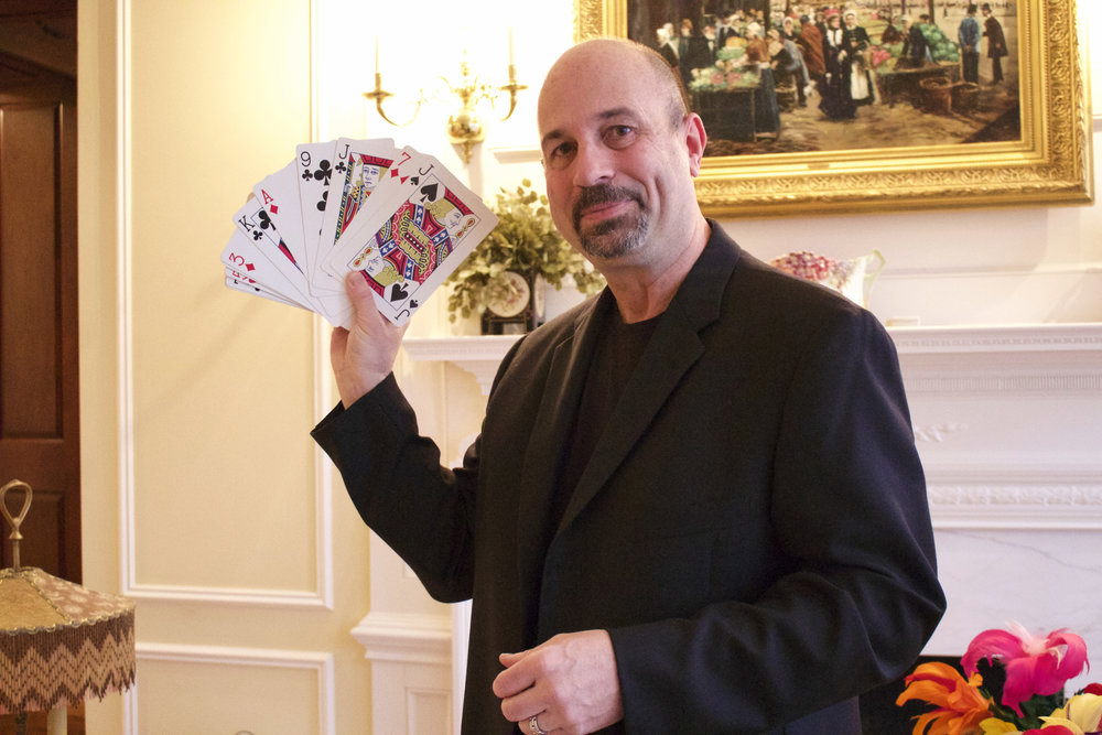 Christopher Homer, a health education teacher at the Cold Spring Harbor School District, also doubles as a magician. He's pictured with one of his card tricks.
