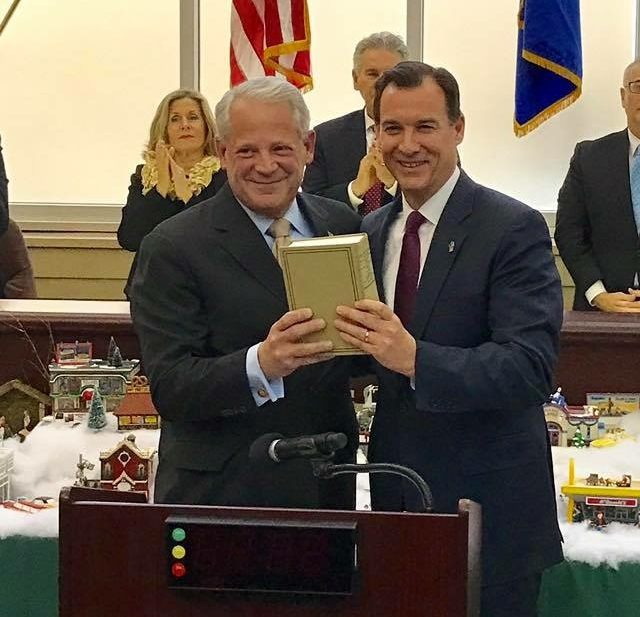 To symbolize the passing of the baton, former Congressman Steve Israel hands over a copy of the House rules and U.S. Constitution to Thomas Suozzi, who will now represent the 3rd Congressional District.