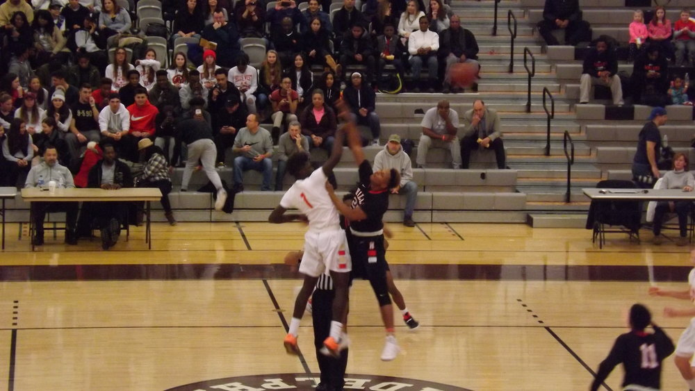 Hills West senior Cameron Jordan, left, and Hills East junior Kenny Mathurin, right, battle for the opening tip-off during Sunday's game at Adelphi University.
