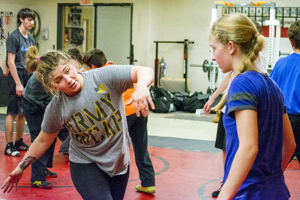 Pvt. Jenna Burkert gives Hills West freshman Nicole Kaplan some pointers during the wrestling clinic at High School East last Thursday.