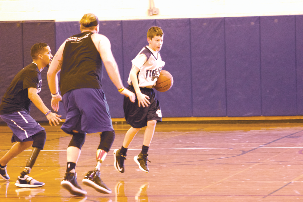Braden Ciszek (no. 31) shields the basketball away from AMP1 players Robert Rodriguez and Nick Pryor at Northport Middle School on Friday.