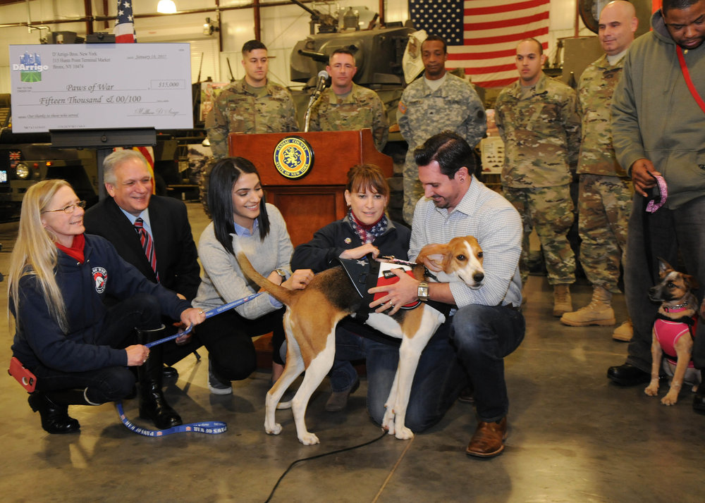 Pictured, from left, are: Lynne Schoepfer, trainer, Paws of War; Nassau Executive Edward Mangano; Gabriela D'Arrigo, marketing and communications director, D'Arrigo Brothers of NY; Dori Scofield, co-founder of Paws of War; and U.S. Navy Veteran Rob Carrozzo and his dog, Lucy.