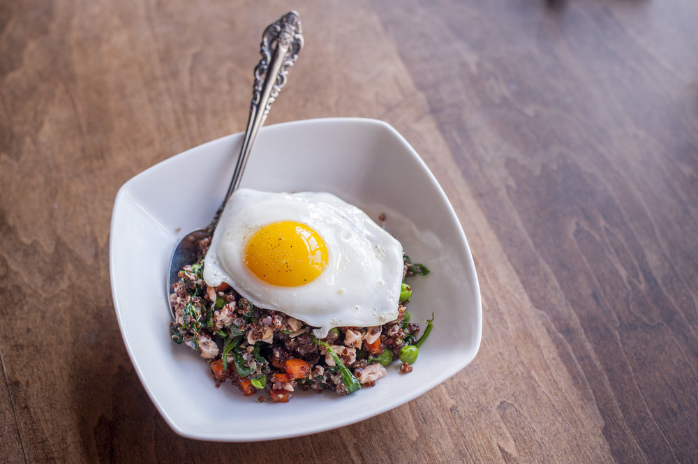 "Skip the takeout fried rice and opt for the healthier and even tastier ""Fried"" Quinoa adorned with peas, carrots and spinach centered around wild salmon all topped with a sunny side up egg."