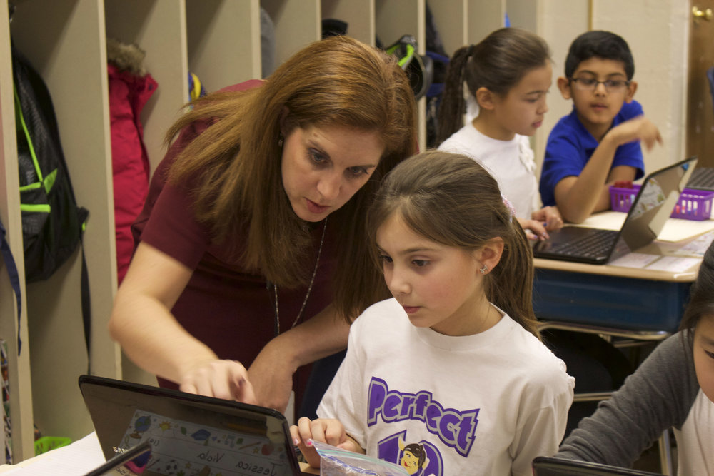 Krista Albrecht, an instructional technology specialist in the Elwood Union Free School District, assists fourth-grader Jessica Viola with a multimedia project.