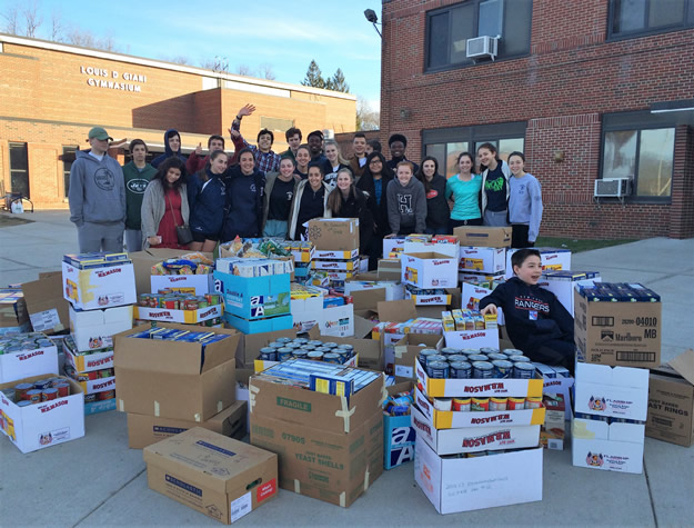 Huntington High School students are pictured last year with the donations collected through the school's annual Stuff The Bus campaign. This year's campaign is currently gearing up.