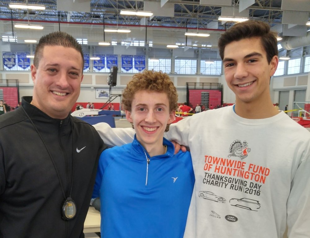 Harborfields coach George Kouroutis, left, stands next to Suffolk's small school 2-mile run champion Matt Katz, center, and Alex Martin, who finished third in the 2-mile event at the Suffolk League IV championships.