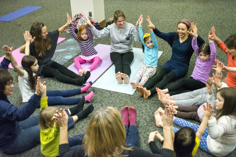 Yoga instructor Alana Andresen ends class with a big group pose, one of the most fun parts about doing family yoga.