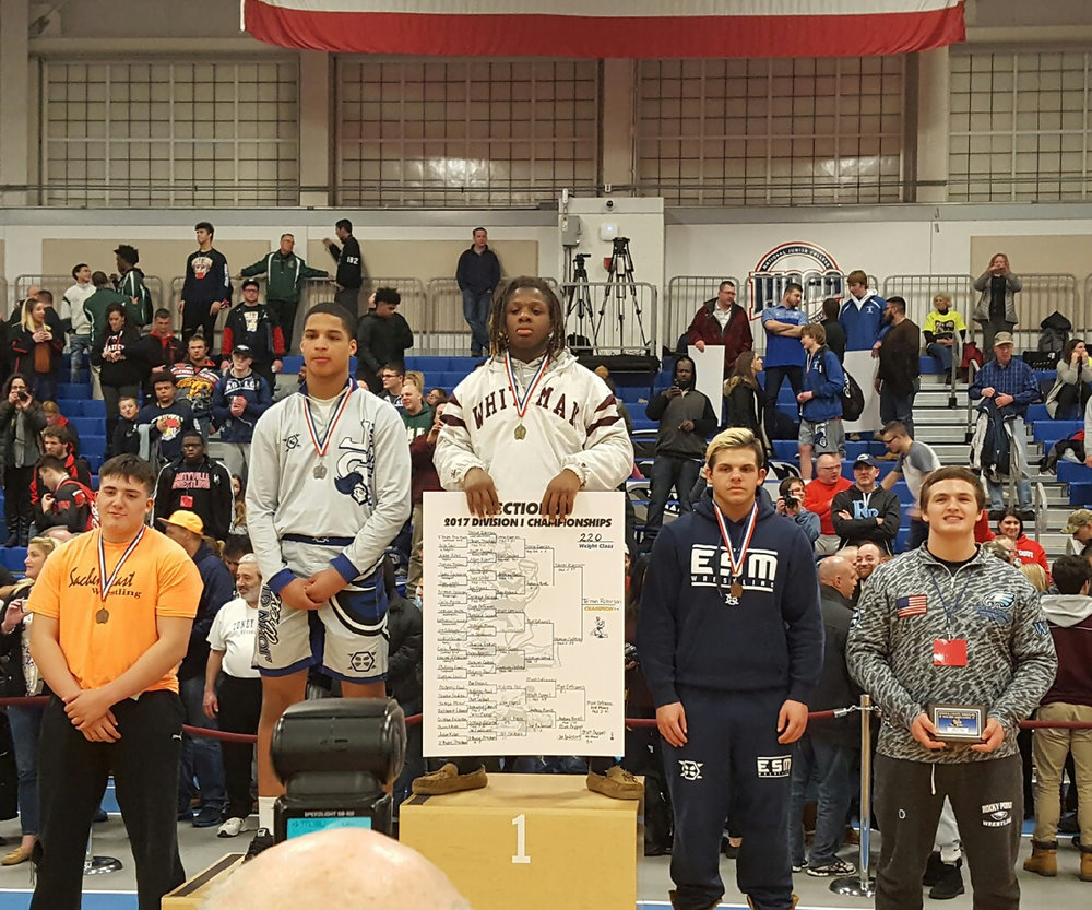 Walt Whitman senior Terron Robinson stands at the top of the podium after claiming Suffolk's championship in the 220-pound weight class. (Photo / Steve Bartholomew)