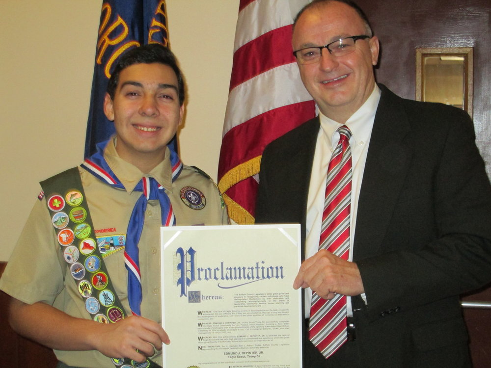 Suffolk Legislator Robert Trotta presents a proclamation to Eagle Scout Eddie DePinter Jr., for the creation of a memorial bench and pear tree in the memory of Northport native and fellow Eagle Scout Cpl. Christopher Scherer.
