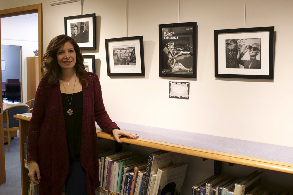 "Alissa Rosenberg standing next to her award winning photography series ""Perfectly Imperfect-Augmented Reality,"" which is on display at the Harborfields Public Library."