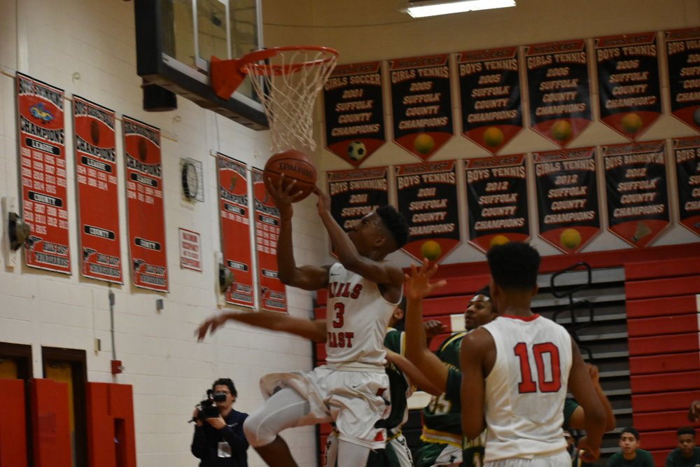 Hills East junior guard Savion Lewis drives through Longwood defenders for a layup.