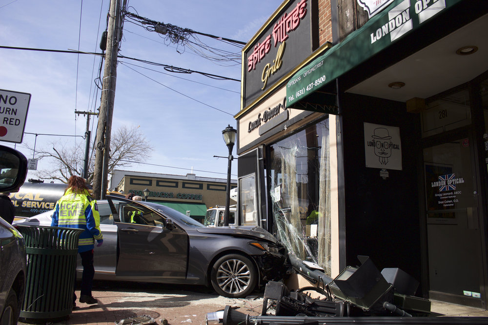 A car crashed into Spice Village Grill this morning when the driver of a grey Chrysler veered into the building to avoid hitting another car on Main Street in Huntington Village.(Long Islander News/Janee Law