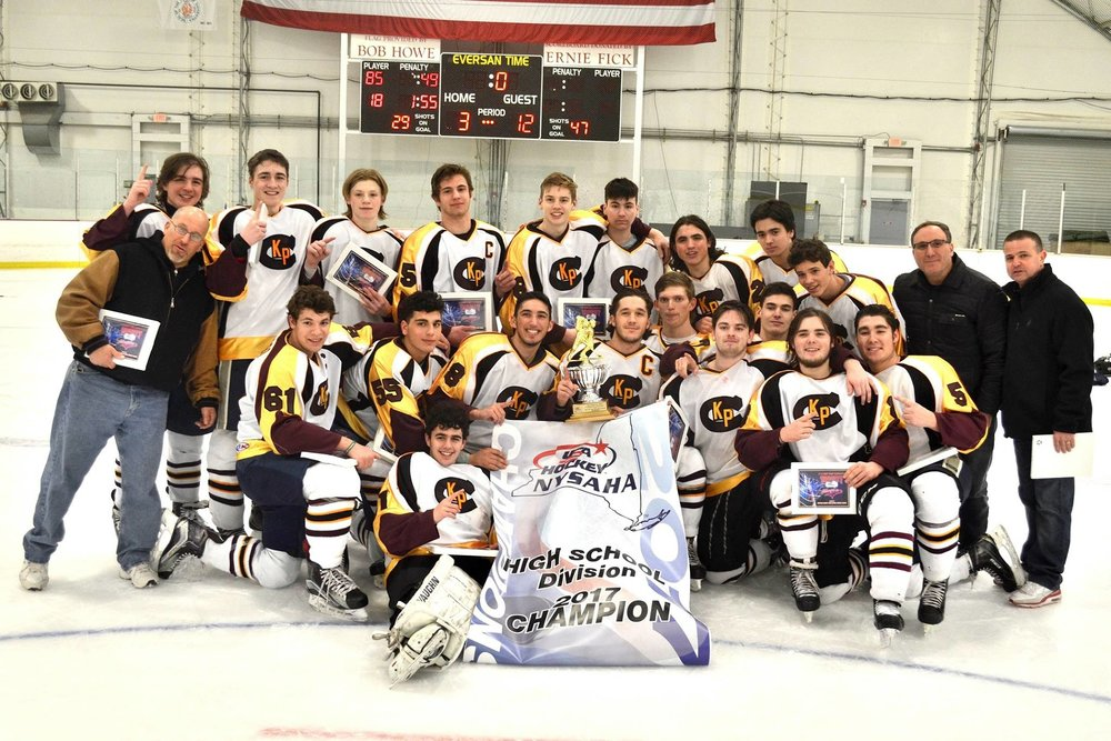 Photo courtesy of Chrissy James Members of the Kings Park-Commack Ice Hockey Club high school team proudly show off their state championship banner. They're pictured with defense coach Dave Kaufman, far left; head coach Steven Dorf, second from right; and offense coach Nicholas Ceccarini, far right.