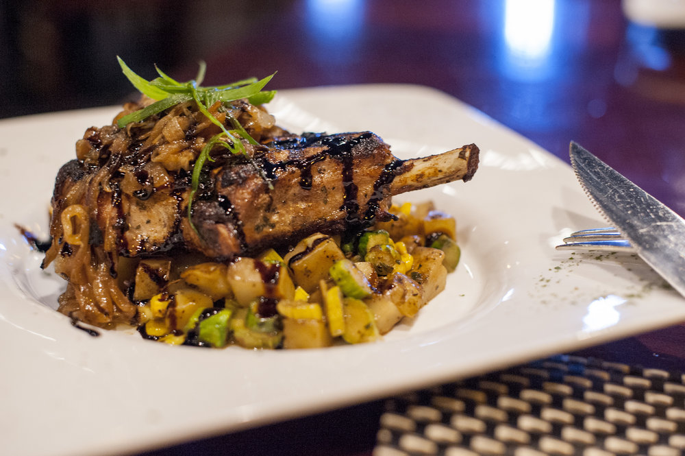 The Pork Chop special plates a rich pork chop, Yukon potato, asparagus, corn fricassee, caramelized onion, with a drizzle of balsamic glaze as a delightful balance of sweet and savory tones.