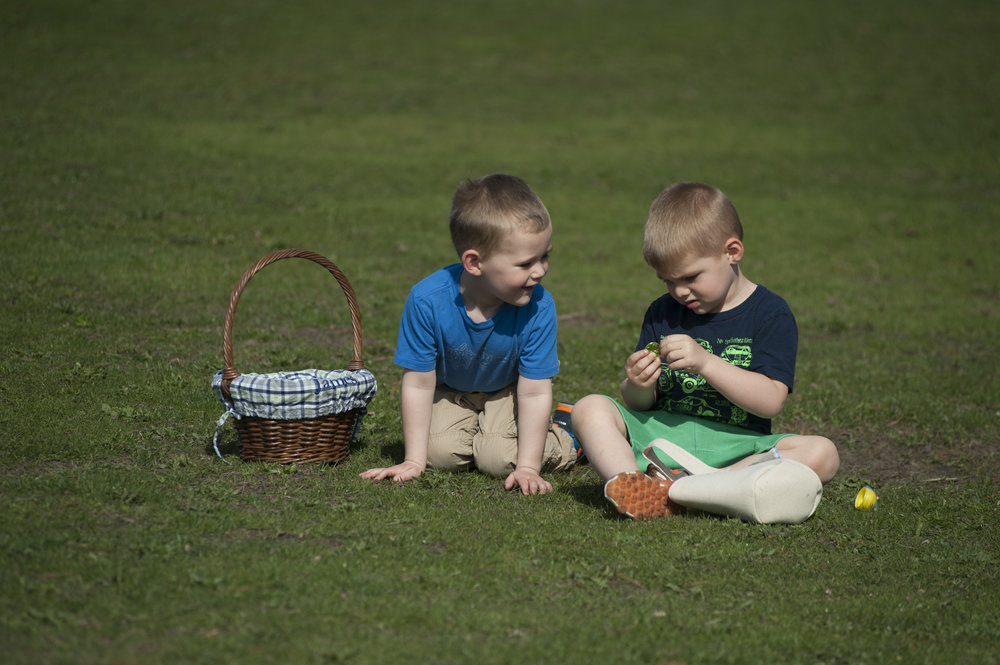 Two brothers rummage through their Easter eggs to see what candy and toys lie within at 'Eggstravaganza,' at Heckscher Park Tuesday. Scores of children participated in the egg hunt, and annual event hosted by the Town of Huntington.
