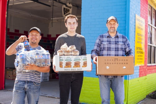 Long Islander News photo/Jano Tantongco  From right, Pastor Enrique Carbajal, who runs the La Misión food pantry, holds boxes of food with his son Juan Pablo Carbajal and church member Carlos Zavala.