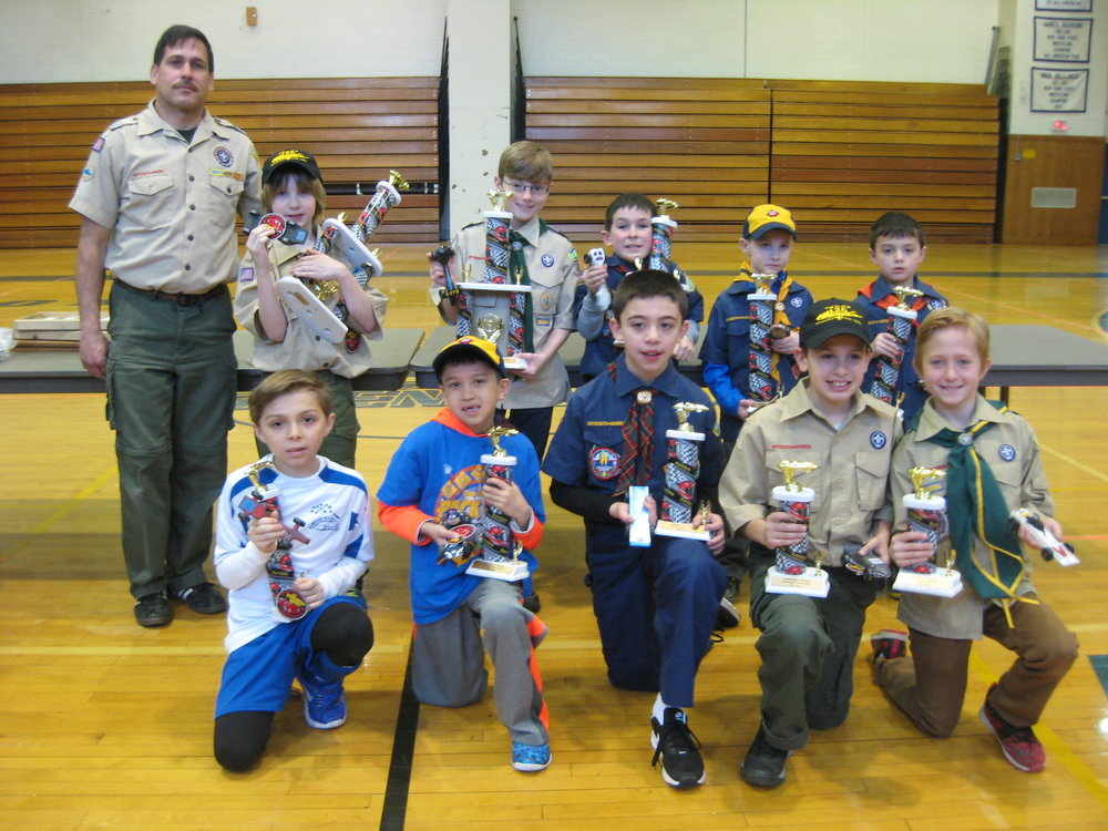 """Top district winners, from right, were: (front row) Gregory M, 1st place, ofPack 329, Commack; Aidan L., 2nd place, ofPack 52, East Northport; Mario M., 3rd place, ofPack 5, Northport; Jack R., 4th place, ofPack225, Greenlawn; and, standing in for 5th-place winner, """"JJ"""" S., ofPack329, is Nolan M. Also pictured in the back row are: Sebastian P., 6th place, ofPack 471, Elwood; Christopher R., 7th place, of Pack406, South Huntington; Dominic S., 8th place, of Pack 5; Matthew M., , 9th place, of Pack 329; Thomas C., 10th place, of Pack 66, South Huntington; and Rob Zeblisky, Matinecock District Pinewood Derby Race chair."""