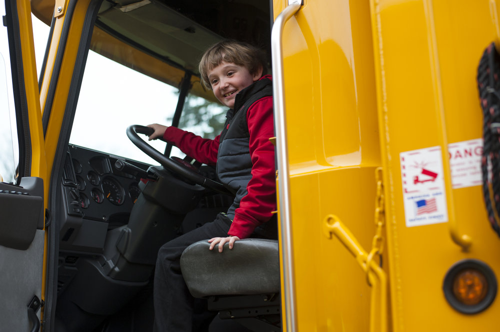 Ryan Chapman honks the horn of a Mack dump truck as his parents try persuading him to let the next child have a turn. For a brief moment, kids had an opportunity to sit in the driver's seat of several work vehicles, including two NYPD police cars, a garbage truck, and a plow.