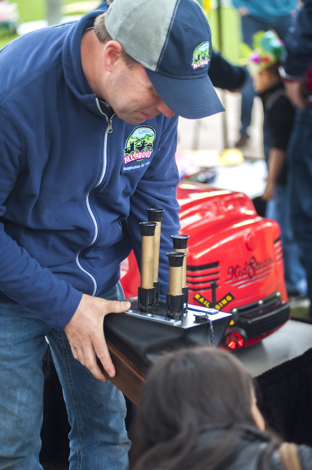 A representative from All Aboard: Imagination at Work, a company that provides kid-powered locomotives and model trains for events and parties, blows the horn of one of the train chimes on display before handing it off to a young boy for a turn.