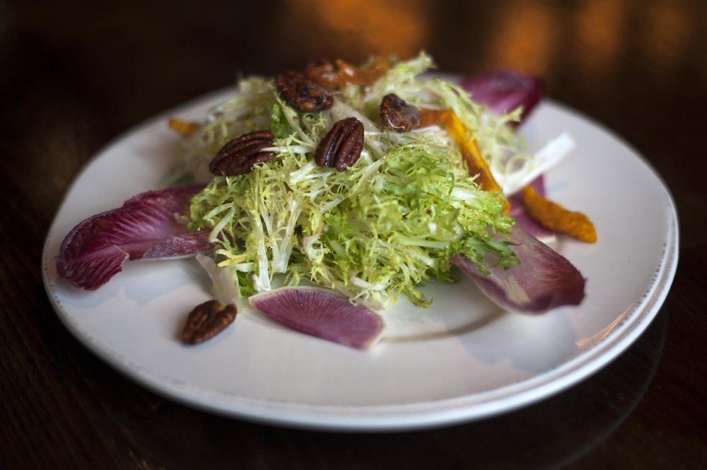 The Organic Bistro Salad features frisee, endive, watermelon radish, candied pecans, dried peaches and topped with sherry citrus dressing.